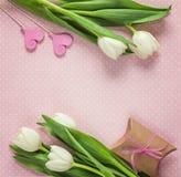 Tulipas, corações e caixa de presente brancos no fundo rosado Traça feliz Fotos de Stock
