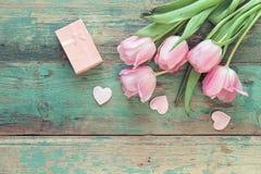 Tulipas, corações e caixa de presente cor-de-rosa em vagabundos de madeira de um grunge de turquesa Fotografia de Stock