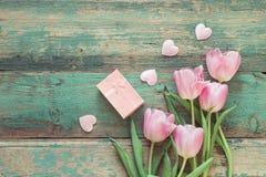 Tulipas, corações e caixa de presente cor-de-rosa em vagabundos de madeira de um grunge de turquesa Imagem de Stock