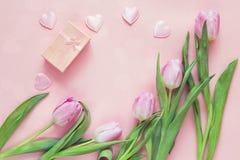 Tulipas, corações e caixa de presente cor-de-rosa no fundo rosado Wi da vista superior Fotos de Stock Royalty Free