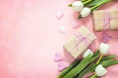 Tulipas, corações e caixas de presente brancos no fundo cor-de-rosa Mo feliz Fotografia de Stock Royalty Free