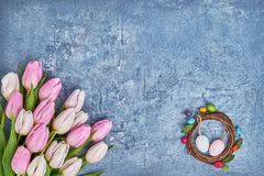 Tulipas da grinalda da Páscoa, as brancas e as cor-de-rosa, ovos da páscoa decorativos no fundo azul Vista superior Fotografia de Stock Royalty Free