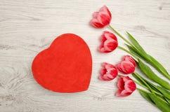 Tulipas dadas forma e cor-de-rosa do coração vermelho da caixa em um fundo de madeira claro Vista superior, espaço para o texto Foto de Stock Royalty Free