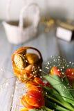 Tulipas de florescência perto de uma cesta com bolinhos de amêndoa Imagens de Stock Royalty Free