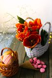 Tulipas de florescência perto de uma cesta com bolinhos de amêndoa imagens de stock