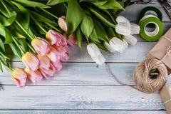 Tulipas de Multicolored do florista do local de trabalho em um fundo de madeira horizontal Vista superior fotografia de stock royalty free