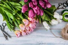 Tulipas de Multicolored do florista do local de trabalho em um fundo de madeira horizontal Vista superior imagens de stock