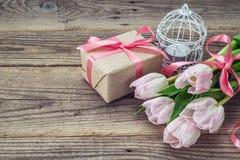 Tulipas e caixa de presente cor-de-rosa com a fita rosado em vagabundos de madeira de um grunge imagens de stock