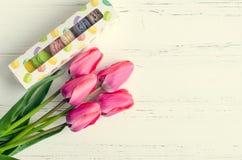 Tulipas e caixa de presente cor-de-rosa com bolinhos de amêndoa Fotografia de Stock