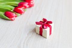 Tulipas e caixa de presente vermelhas com curva vermelha Fotos de Stock Royalty Free