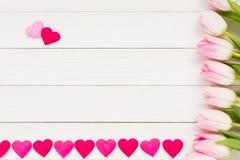 Tulipas e coração cor-de-rosa no fundo de madeira branco Vista superior, fundo do feriado, Valentine Day Fotos de Stock