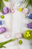 Tulipas e ovos da páscoa roxos do ramalhete em uma tabela de madeira clara Imagem de Stock