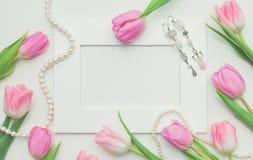 Tulipas, quadro da foto, brincos e corda cor-de-rosa das pérolas no fundo branco com espaço da cópia Vista superior Fundo bonito  Fotos de Stock