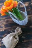 Tulipas que florescem em uma cesta em um fundo de madeira imagens de stock
