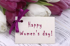 Tulipas roxas e brancas com Livro Branco em um fundo e em um cartão de madeira brancos que rotulam o inglês feliz do dia do ` s d Fotos de Stock Royalty Free