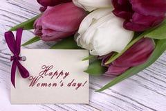 Tulipas roxas e brancas com Livro Branco em um fundo e em um cartão de madeira brancos que rotulam o inglês feliz do dia do ` s d Fotografia de Stock Royalty Free