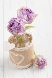 Tulipas roxas na garrafa com corações Fotografia de Stock Royalty Free