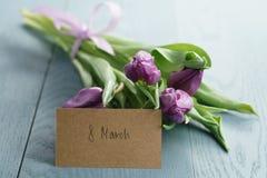 Tulipas roxas no papel do ofício no fundo de madeira azul com cartão do 8 de março Fotos de Stock