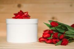 Tulipas vermelhas bonitas com um presente Curva vermelha em um presente em um fundo de madeira fotos de stock royalty free