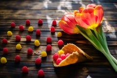 Tulipas vermelhas de florescência em um fundo de madeira com doces Fotos de Stock