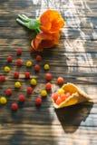 Tulipas vermelhas de florescência em um fundo de madeira com doces Foto de Stock Royalty Free