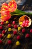 Tulipas vermelhas de florescência em um fundo de madeira com doces Imagens de Stock Royalty Free
