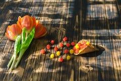 Tulipas vermelhas de florescência em um fundo de madeira com doces Foto de Stock