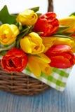 Tulipas vermelhas e amarelas em uma cesta Fotografia de Stock Royalty Free