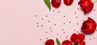 Tulipas vermelhas e confetes dados forma cora??o no espa?o colocado liso cor-de-rosa pastel da c?pia da opini?o superior do fundo imagens de stock
