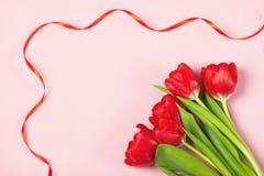 Tulipas vermelhas em um fundo cor-de-rosa Fotografia de Stock