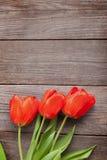 Tulipe de trois rouges sur le vieux tableau noir en bois grunge rustique, Photographie stock