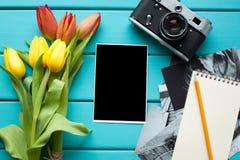 Tulipes, appareil-photo de vintage rétro et bloc-notes avec le crayon, et photos de finition sur un fond en bois bleu Images libres de droits