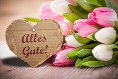 Tulipes avec le message indiquant meilleurs voeux ! en allemand Photographie stock
