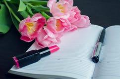 Tulipes avec le stylo et le rouge à lèvres sur le carnet vide Images stock
