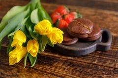 Tulipes, biscuits et fraises jaunes sur une table en bois Un cadeau gentil pour votre aimé Un bouquet des tulipes et d'un festin Photos stock