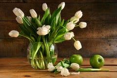 Tulipes blanches dans le vase en verre sur le bois rustique Images libres de droits