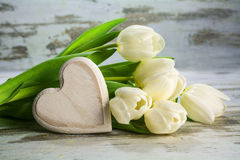 Tulipes blanches et un coeur de bois sur un backgr en bois gris de vintage Photo libre de droits