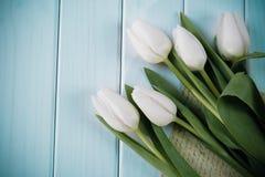 Tulipes blanches sur le fond de turquoise Lettre et tulipes de ressort Image stock