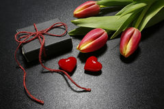 Tulipes, boîte-cadeau et coeurs rouges Photographie stock