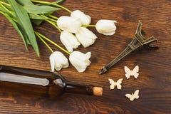 Tulipes, bouteille de vin et Tour Eiffel miniaturisé Photographie stock libre de droits
