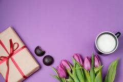 Tulipes, café et bonbons pourpres sur un fond violet Ressort Photos libres de droits