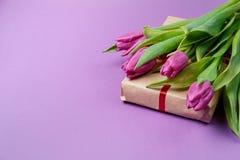 Tulipes, café et bonbons pourpres sur un fond violet Ressort Photos stock