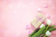Tulipes, coeurs et boîte-cadeau blancs sur le fond rose Mite heureuse Photographie stock libre de droits