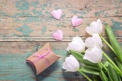 Tulipes, coeurs et boîte-cadeau blancs sur une turquoise b en bois grunge Photos stock
