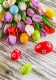 Tulipes colorées avec des oeufs de pâques sur la table en bois Images stock