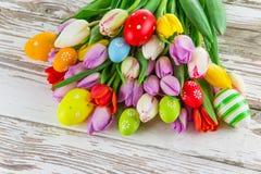 Tulipes colorées avec des oeufs de pâques sur la table en bois Image libre de droits