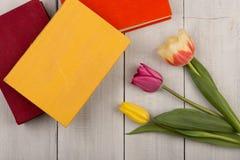 Tulipes de fleurs et livres colorés sur la table en bois blanche Photographie stock libre de droits