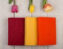 Tulipes de fleurs et livres colorés sur une table en bois blanche Photographie stock