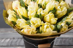 Tulipes doucement jaunes de couleurs en pastel dans le vase sur la table en bois Mur gris Photo stock