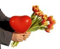 Tulipes et ballon rouge sous forme de coeur dans des mains des hommes Photographie stock libre de droits
